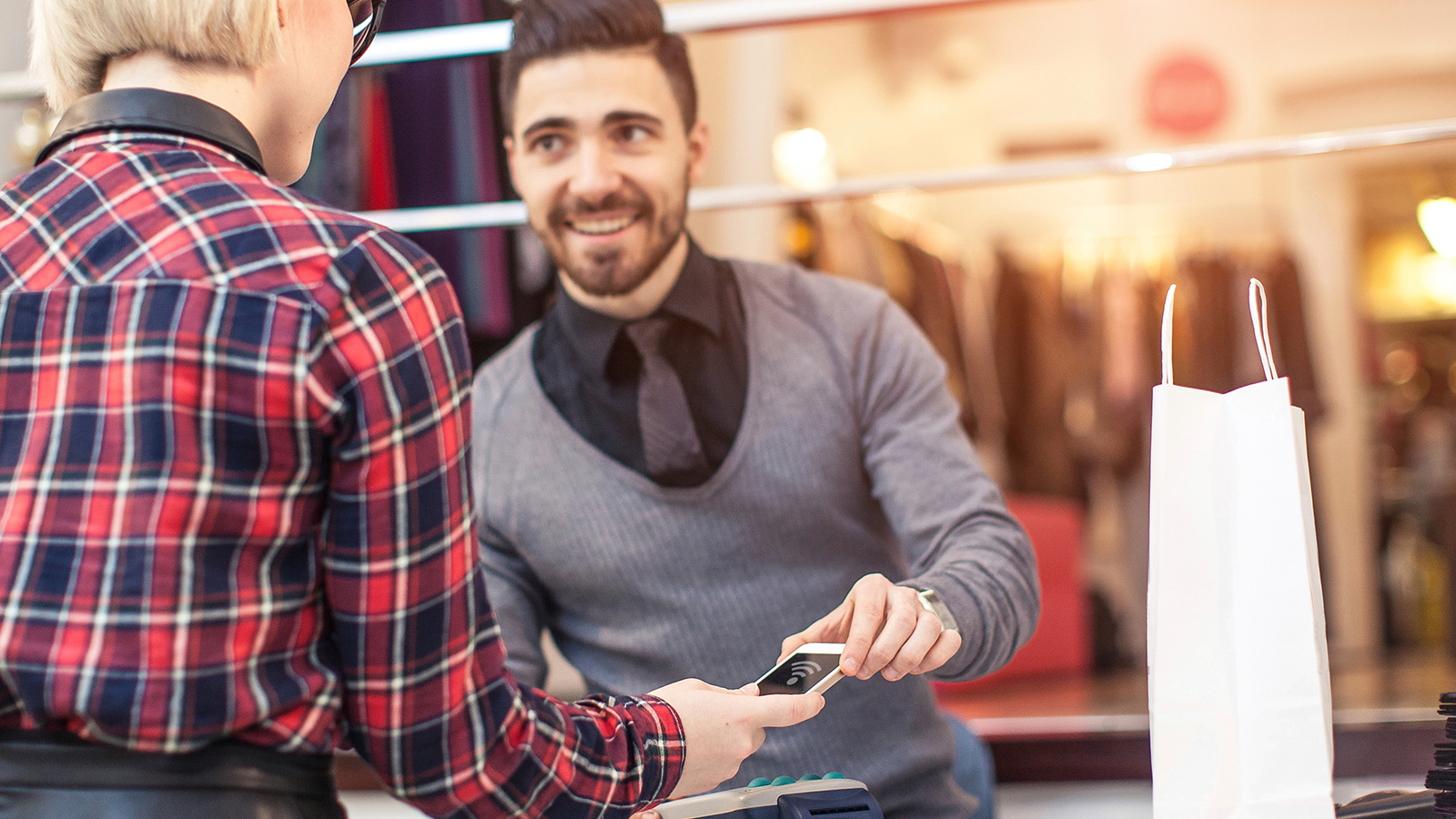 A sales person assisting with a contactless transaction by showing a customer where to hover a mobile phone.