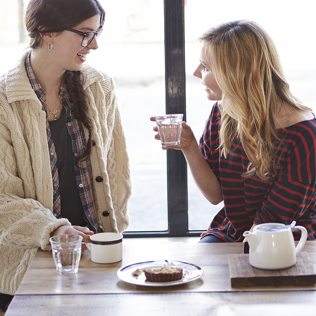 Two women talking in a coffee shop.