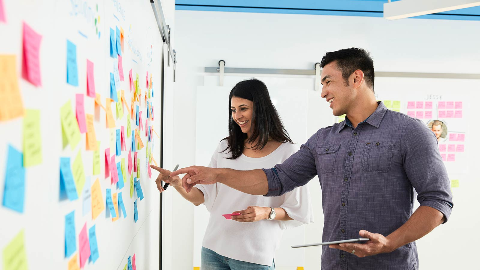 Man and woman in front of whiteboard with sticky notes of innovative ideas.