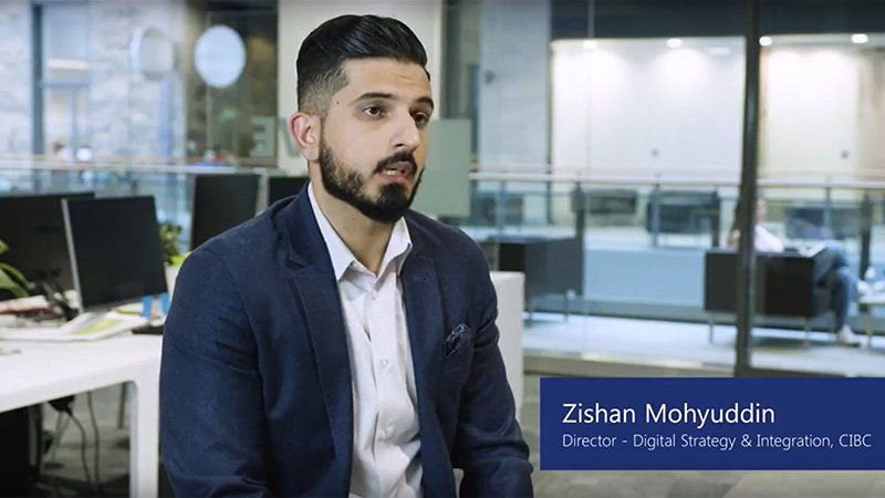 Man named Zishan Mohyuddin, Director of Digital Strategy and Integration at CIBC, sits in office and talks to camera.